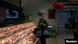 一名戴着口罩的互联网供货商在北京亦庄一家肉店为网上订户购买猪肉。(2020年2月8日)