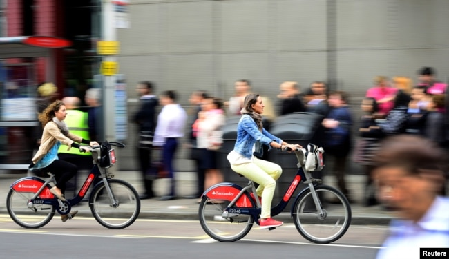 FILE - Commuters cycle past a bus stop outside Waterloo Station in London, Britain August 6, 2015.