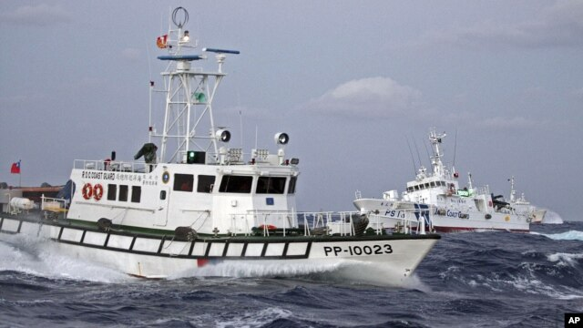 In this photo released by Taiwan's Central News Agency, a Taiwan Coast Guard patrol boat, front, comes in close proximity with a Japan Coast Guard patrol boat near the disputed islands called Senkaku in Japan and Diaoyu in China, in the East China Sea, Se