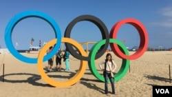 یک دختر جوان در ریو می خواهد کنار علامت المپیک عکس بگیرد.