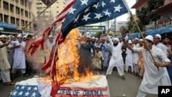 孟加拉的游行示威者们焚烧美国国旗