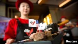 在北京举行的一个庆祝美国牛肉进口中国的活动上,一名推销员请与会来宾品尝美国牛肉 (资料照片)