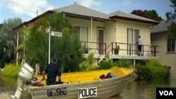 Seorang polisi Australia menggunakan perahu kecil untuk memeriksa kawasan yang terkena banjir.
