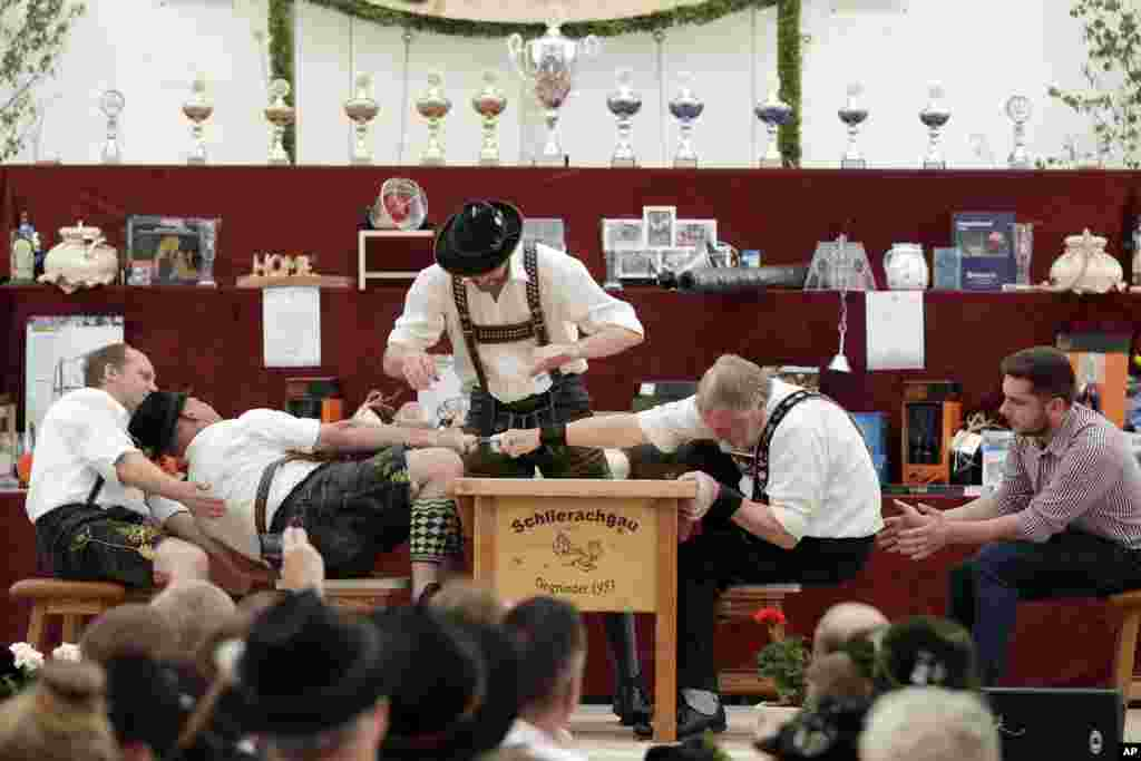 A man dressed in traditional clothes tries to pull his opponent over the table at the 40th Alpine Country Championships in Fingerhakeln in Woernsmuehl, , Germany.