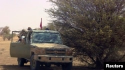 Des combattants du groupe séparatiste rebelle MNLA, à bord d'un véhicule 4x4, s'abritent à l'ombre d'un arbre près de Tabankort, Mali, le 15 février 2015 (Archives)