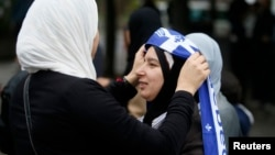 FILE - A demonstrator adds a Quebec flag to her veil during a protest against Quebec's proposed Charter of Values in Montreal, Sept. 14, 2013. Thousands took to the streets to denounce the province's proposed bill to ban the wearing of any overt religious clothing by government-paid employees or people seeking government services.
