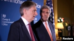 Menlu AS John Kerry (kanan) mendengarkan penjelasan Menlu Inggris Philip Hammond dalam pertemuan dengan anggota koalisi membahas isu terkait ISIS di Lancaster House, London (22/1).