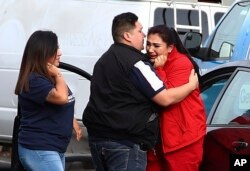 Fernando Juarez, 36, of Napa, center, embraces his 22-year-old sister Vanessa Flores, right, at the Veterans Home of California, March 9, 2018, in Yountville, Calif. Flores, who is a caregiver at the facility, exchanged texts with family while sheltering in place during a hostage situation, which ended with four people dead.