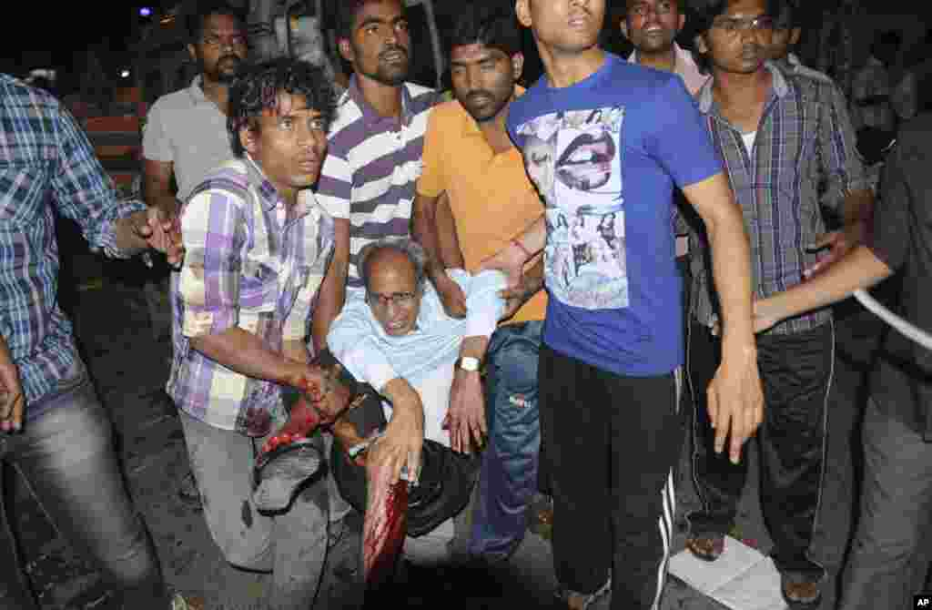 People rescue an injured person after a bomb blast in Hyderabad, India, February 21, 2013.