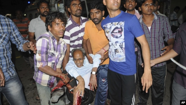 People rescue an injured person after a bomb blast in Hyderabad, India, Feb. 21, 2013.
