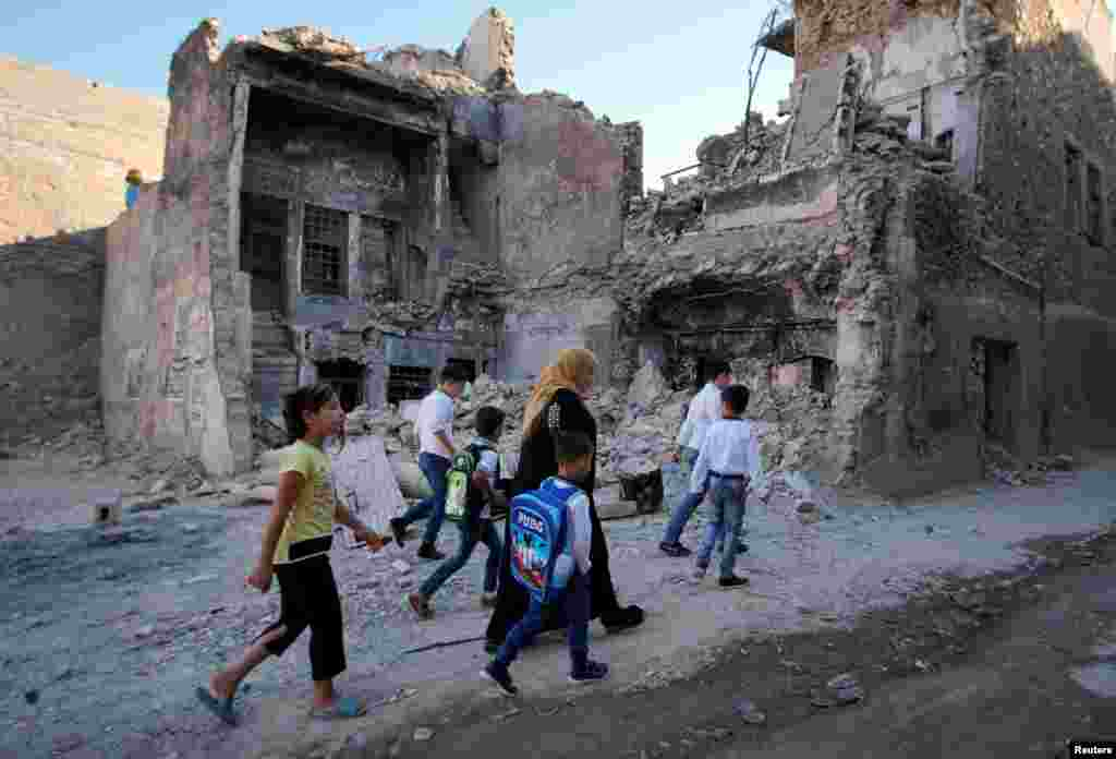 A woman walks with her kids on the first day of the new school term in the old city of Mosul, Iraq.