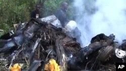 Foto yang diambil dari gambar di televisi yang ditayangkan tanggal 16 Desember ini menayangkan puing-puing helikopter yang jatuh dan terbakar di negara bagian Bayelsa di Nigeria, Sabtu (15/12). Gubernur Patrick Yakowa dan mantan penasihat keamanan nasional Nigeria, Jendral Andrew Azazi dilaporkan tewas dalam kecelakaan ini.