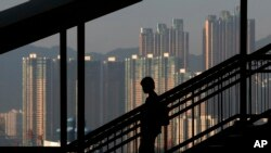FILE - A woman walks down a stairway against the backdrop of high-rise apartment buildings in Hong Kong.