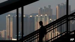 一位女士沿步道而下,背景是香港的摩天大楼。(资料照)