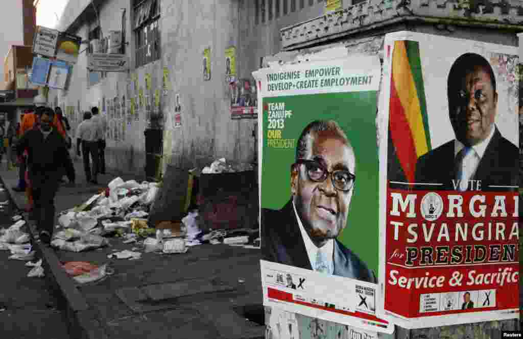 Election campaign posters are pictured near Zimbabweans walking on a street blocked by uncollected garbage in Harare July 17, 2013. President Robert Mugabe's rivals said the chaotic organisation of early voting for soldiers and police showed Zimbabwe was not ready for the July 31 general election in which nearly six million people had registered to vote.