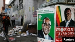 FILE: Election campaign posters are pictured near Zimbabweans walking on a street blocked by uncollected garbage in Harare July 17, 2013.
