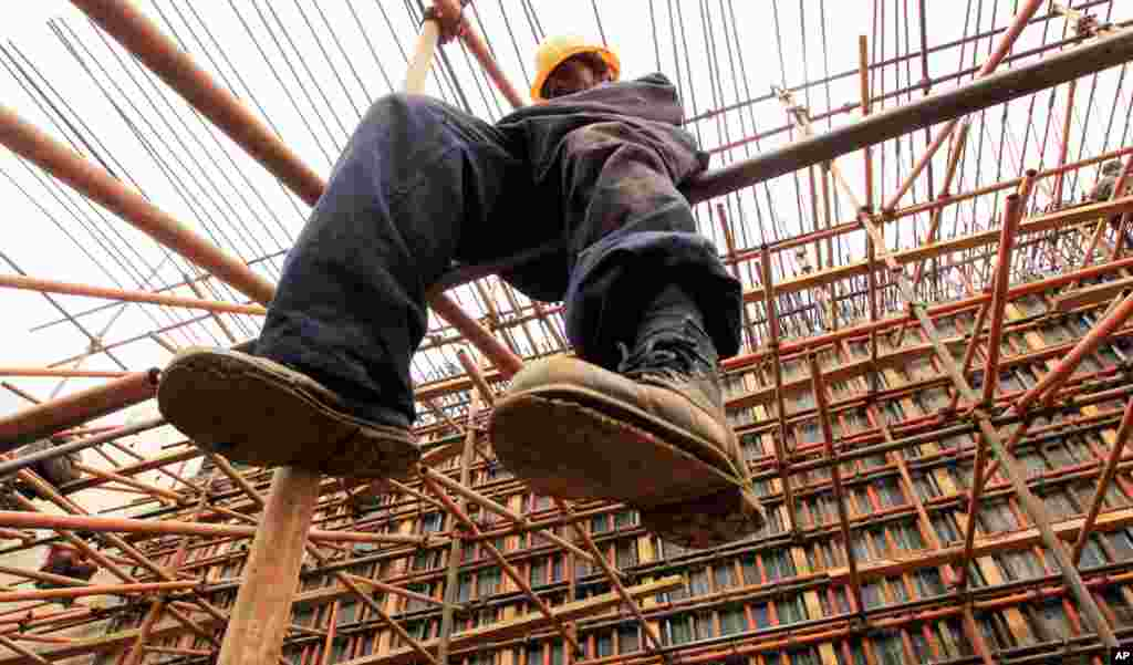 A construction worker erects scaffolding on a new bridge along the Nairobi-Thika highway project, under construction near Kenya's capital Nairobi, September 13, 2010. The road, built by China Wuyi, Sinohydro and Shengeli Engineering Construction group, is