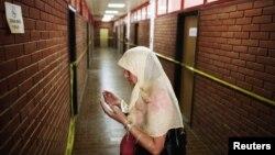 Seorang perempuan Muslim Bosnia berdoa di koridor ruangan-ruangan tempat tahanan disiksa pada peringatan 20 tahun penutupan kamp penahanan Omarska di Bosnia dan Herzegovina awal Agustus. (Foto: Reuters)