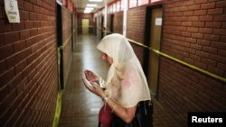 A Bosnian Muslim woman prays along a corridor with rooms where inmates were tortured, during the 20th anniversary of the closure of the Omarska detention camp in Omarska, Bosnia and Herzegovina, August 6, 2012.
