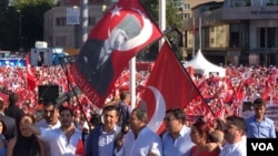 Demonstrators at Taksim Square wave flags bearing the face of Mustafa Kemal Ataturk, revered as founder of the modern Turkish Republic, July 24, 2016. Many are calling for preservation of the secular state established by Ataturk nearly a century ago. (L. Ramirez/VOA)