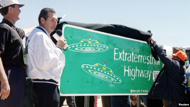 An April 18, 1996 file phoso shows a Nevada Governor Bob Miller (C), presiding over the unveiling of a new road sign for Nevada State Highway 375, the site for many UFO sightings, in  Rachel, north of Las Vegas.