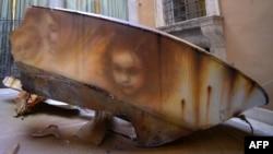 Graffitis de l'artiste de rue italien Eron sur la coque d'un bateau brisé montrant les visages d'une femme migrante et d'enfants, Rome, 14 avril 2016.