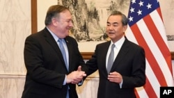 Chinese State Councilor and Foreign Minister Wang Yi, right, talks with U.S. Secretary of State Mike Pompeo, left, before a meeting at the Diaoyutai State Guesthouse in Beijing, Oct. 8, 2018.