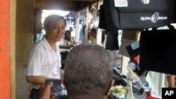 A Chinese salesman sells consumer goods in Abidjan, Ivory Coast