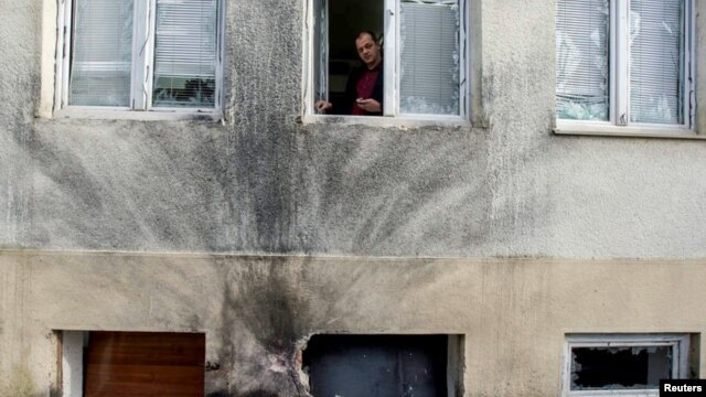 FILE - Editor-in-chief of Montenegro's leading daily Vijesti, Mihailo Jovovic looking through a window damaged in a bomb blast at the newspaper's offices in Podgorica, Dec. 27, 2013