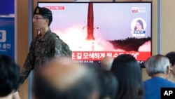 A South Korean army soldier passes by a TV screen showing a file image of North Korea's missile launch during a news program at the Seoul Railway Station in Seoul, South Korea, Tuesday, Aug. 6, 2019.