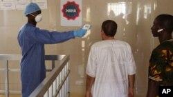 Seorang petugas kesehatan mengukur suhu badan seorang pria untuk memerika apakah ia terinfeksi oleh virus ebola di Conakry, Guinea (18/3). WHO mengaku bahwa sejumlah kecil kasus Ebola masih terjadi di Guinea.