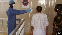Un agent de santé prend la température des personnes pour voir si elles pourraient être infectés par le virus Ebola dans l'hôpital du gouvernement Ignace Deen à Conakry, en Guinée, le 18 Mars 2016. (AP Photo/Youssouf Bah)