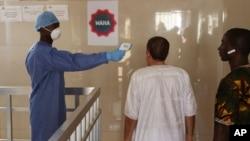 Un agent de santé, à gauche, prend la température des quelques personnes à l'hôpital gouvernemental Ignace Deen à Conakry, en Guinée, 18 mars 2016.