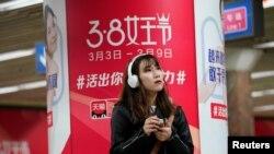 Seorang perempuan berdiri di depan iklan platform e-commerce Alibaba, di stasiun kereta bawah tanah di Beijing, Cina 7 Maret 2018. (Foto: REUTERS/Jason Lee)