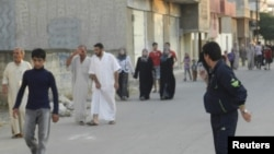 Dân chúng ở Houla, gần thành phố Homs của Syria, chạy khỏi nhà sau khi bị pháo kích