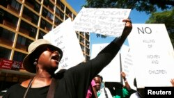 Women protest outside the Pretoria Magistrates court, during the bail application hearing of South African athlete Oscar Pistorius, February 19, 2013.