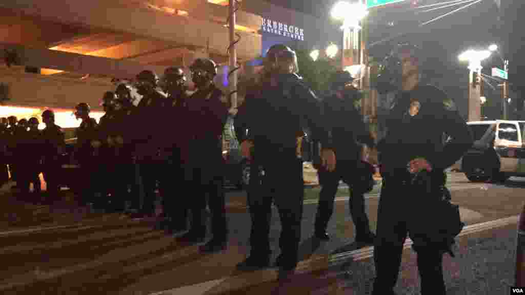 Arizona police officers activate anti-riot procedures after people report being attacked with water bottles, in Phoenix, Az., Aug. 22, 2017. (Photo: Celia Mendoza / VOA)