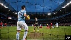 Pemain Manchester City, Sergio Aguero mengambil bola dari net setelah sebuah gol dari kawan satu timnya Yaya Toure dalam pertandingan dengan Cardiff City, Januari. (AP/Jon Super)