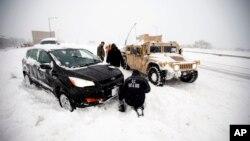 Binh sĩ và lính cứu hỏa trên chiếc Humvee giúp một người lái xe bị mắc kẹt trong tuyết trên đường I-395 tại Washington.