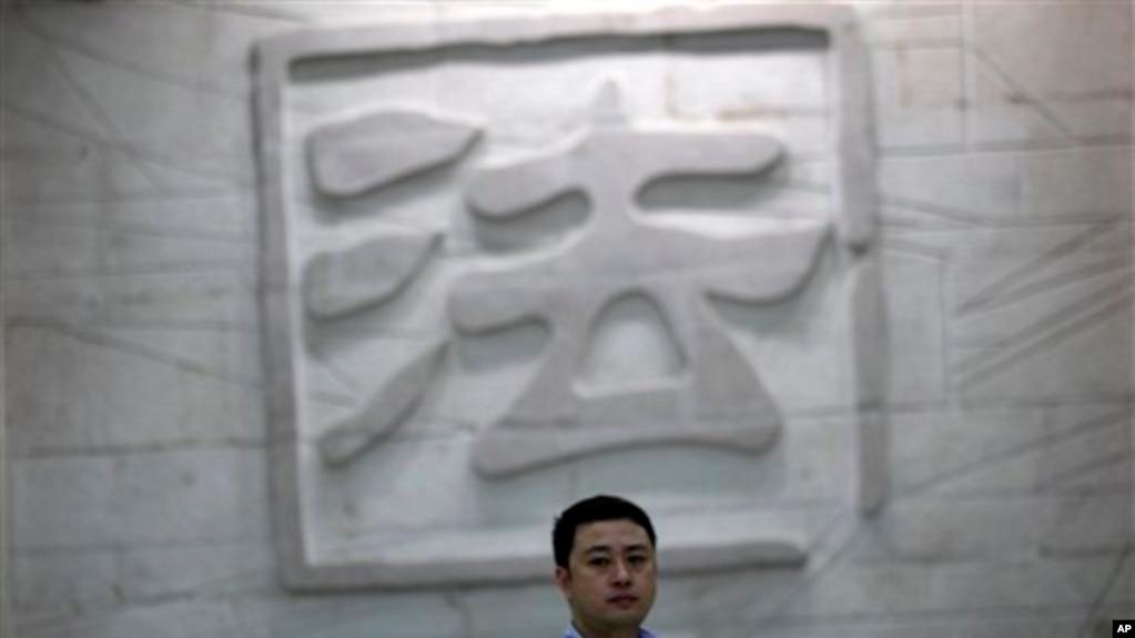 """一名男子走過中國一家法院刻有""""法""""字的牆壁。 (資料照片)"""