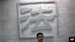 """Seorang pria melewati tulisan berbahsa Mandarin yang berarti """"Hukum"""" dalam gedung pengadilan di Kota Hefei, provinsi Anhui, China (Foto: dok). Pemerintah China tengah menyelidiki mantan wakil gubernur wilayah ini karena diduga terlibat kasus korupsi."""