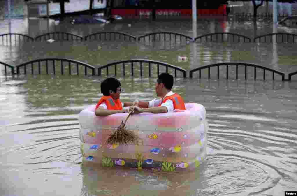 Men sit in an inflatable tub along a flooded street as heavy rainfall hits Lishui, Zhejiang province, China, Aug. 20, 2014.