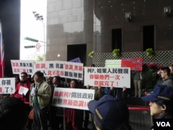 就职典礼会场外抗议民众举标语警告新任市长柯文哲(美国之音许波拍摄)