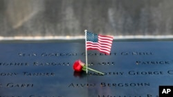 Joined by a solitary red rose, a small American Flag is stuck into an etched name on the wall at the National September 11th Memorial.