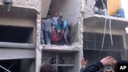 19일 시리아 정부군의 알레포 폭격으로 폐허가 된 건물에서 부상자를 옮기고 있다.
