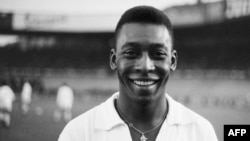 """L'attaquant brésilien Pelé, vêtu de son maillot Santos, sourit avant de disputer un match de football amical avec son club contre le club français du """"Racing"""", le 13 juin 1961 à Colombes en France."""