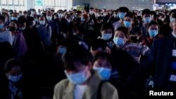 五一长假前人们戴着口罩在上海火车站排队。 (2021年4月30日)
