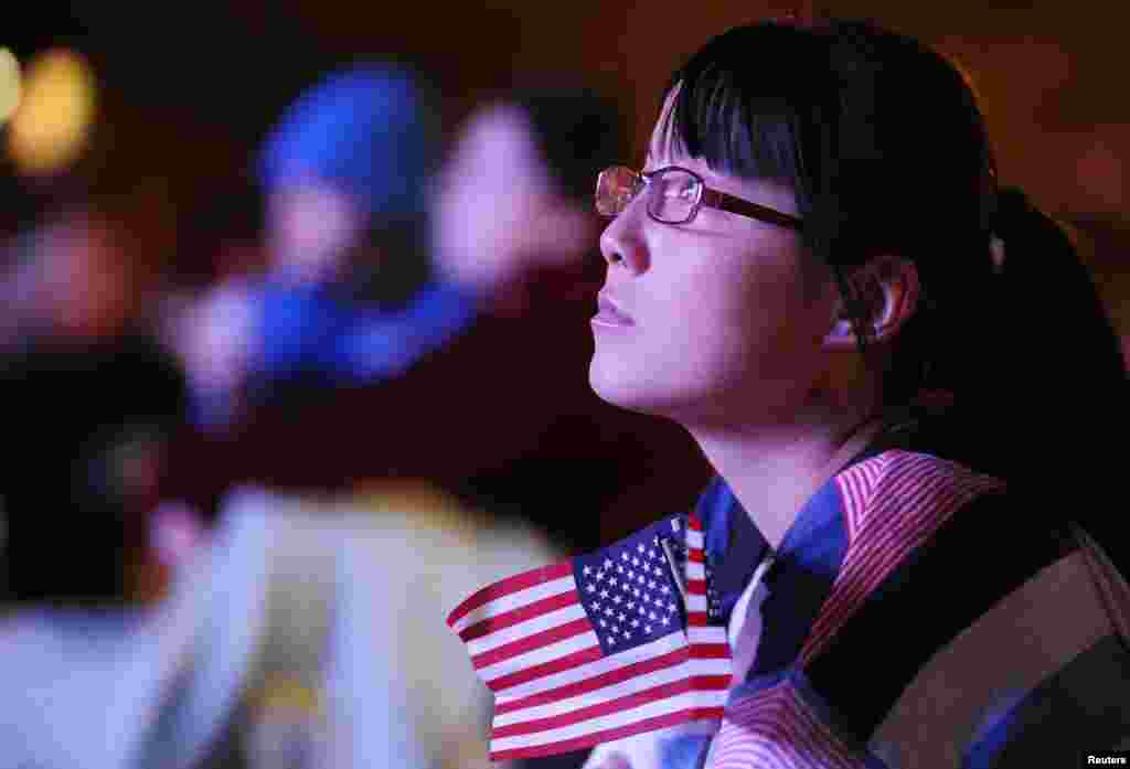 Kim Li, a junior at Denver University, watches the first 2012 U.S. presidential debate between President Barack Obama and Republican presidential nominee Mitt Romney on an outdoor screen at Denver University in Denver, Colorado, October 3, 2012.