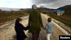 Siriyalik ayol farzandlari bilan Turkiya chegarasi yaqinidagi qochqinlar lagerida boshpana topgan.