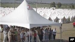 叙利亚难民在土耳其和叙利亚边界附近的一所难民营里祷告